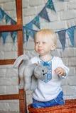 一个滑稽的小男孩的画象有玩具小猫的 免版税库存照片