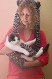 一个滑稽的帽子的女孩拿着一只猫 库存图片