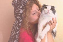 一个滑稽的帽子的女孩拿着一只猫 图库摄影