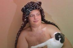 一个滑稽的帽子的男孩拿着一只猫,看彼此的他们充满惊奇 图库摄影