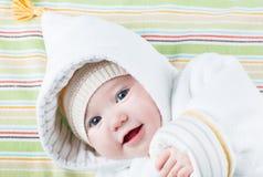 一个滑稽的帽子的逗人喜爱的婴孩在一条五颜六色的毯子 免版税库存图片