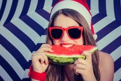 一个滑稽的微笑的女孩的画象在圣诞老人帽子 免版税库存图片