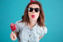 一个滑稽的时髦的女孩的画象显示舌头的太阳镜的 免版税库存照片