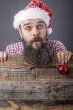一个滑稽的有胡子的人的画象有举行一红色rou的圣诞老人盖帽的 免版税库存照片