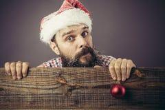 一个滑稽的有胡子的人的画象有举行一红色rou的圣诞老人盖帽的 免版税库存图片