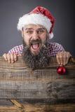 一个滑稽的有胡子的人的画象有举行红色12月的圣诞老人盖帽的 免版税图库摄影