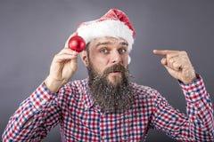 一个滑稽的有胡子的人的画象有圣诞老人盖帽藏品和展示的 免版税库存图片