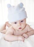 一个滑稽的蓝色帽子的逗人喜爱的男婴 图库摄影