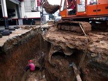 一个建筑人在排水设备管子工作 库存图片