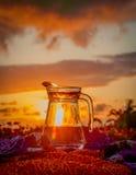 一个水罐在精采日落的背景的饮用水 免版税库存照片