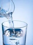 从一个水罐的特写镜头倾吐的水到在一蓝色backgroun的玻璃里 免版税库存照片