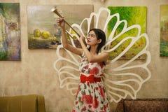 一个年轻美丽的女孩在她的手上站立与一个喇叭 库存照片