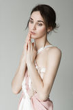 一个年轻美丽的女孩的画象一件浅粉红色的礼服的在灰色背景的演播室 库存图片