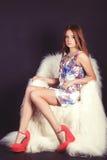 一个年轻美丽的女孩的画象有长的头发的在有花的一件白色礼服在红色拖鞋在一黑backgroun的演播室 免版税库存照片