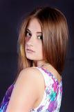一个年轻美丽的女孩的画象有长的头发的在有花的一件白色礼服在黑背景的演播室 免版税库存图片