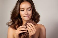 一个年轻美丽的女孩的画象有黑暗的卷发、光秃的肩膀和脖子的,拿着巧克力块享用口味和a 免版税库存图片