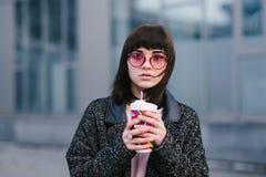 一个年轻美丽的女孩的画象戴桃红色眼镜的和明亮与一杯咖啡在手中 免版税库存图片