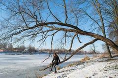 一个年轻美丽的微笑的红色头发欧洲女孩的画象坐树在河附近 免版税库存图片