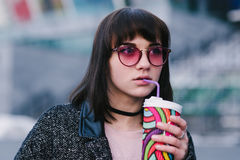一个年轻美丽的时髦的女孩的画象喝与五颜六色的杯子的咖啡的桃红色玻璃行家的 库存图片