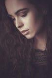 一个年轻美丽的深色的女孩的剧烈的画象有长的卷发的在演播室 免版税库存照片