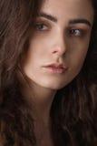 一个年轻美丽的深色的女孩的剧烈的画象有长的卷发的在演播室 免版税库存图片