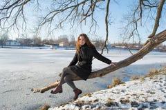 一个年轻美丽的红色头发欧洲女孩的画象坐老树在河附近 库存图片