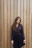 一个年轻美丽的行家女孩的半身画象在摆在户外对木墙壁的时髦的衣裳穿戴了, 免版税库存照片