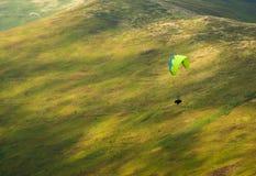 一个滑翔伞飞行在山脉在一个晴朗的夏日 免版税库存图片