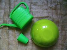 一个绿色半球、一把绿色喷壶浇灌的花的和一块绿色塑料玻璃 免版税库存图片