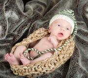 戴一个绿色和白色编织帽子的编织篮子的逗人喜爱的婴孩 库存照片