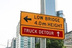 一个黄色和黑'Low桥梁`和'Truck改道`标志 库存照片