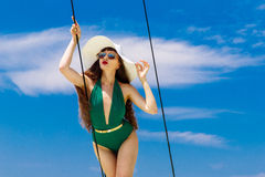一个绿色比基尼泳装和草帽的年轻美丽的女孩,有长期的 免版税图库摄影