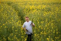 一个黄色油菜籽领域的人在日落的晚上 免版税库存图片