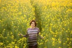 一个黄色油菜籽领域的妇女在日落的晚上 库存照片