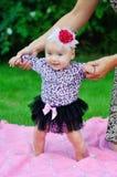 一个绿色草甸的美丽的愉快的矮小的女婴 图库摄影
