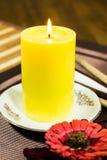 一个黄色蜡烛的构成与一块白色板材和一朵红色花的在桌上 免版税库存图片