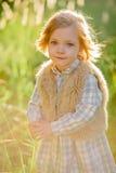 一个绿色领域的逗人喜爱的微笑的女孩在日落 图库摄影
