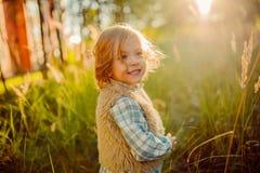 一个绿色领域的逗人喜爱的微笑的女孩在日落 库存图片