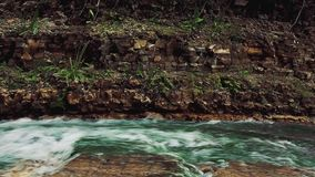 一个黄色鸟卖力的宽射击沿一个岩石水坝的上面的有水池和瀑布的 股票录像