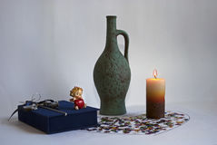 一个绿色水罐和一个被点燃的蜡烛 库存照片