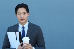 一个年轻英俊的亚洲人商人的画象在黑经典衣服的与时髦蓝色领带 关闭咖啡休息 图库摄影