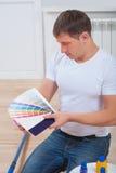 一个年轻英俊的人坐举行颜色palet的木地板 免版税库存照片