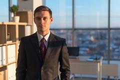 一个年轻英俊的商人的特写镜头画象,严重看照相机,站立在大轻的办公室 免版税图库摄影