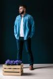 一个年轻英俊的有胡子的人,打扮在牛仔布衬衣和蓝色长裤,站立户内 图库摄影