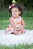 一个绿草公园的小拉丁女孩 免版税库存图片