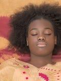 一个年轻蓬松卷发女孩的画象,眼睛关闭了 库存照片