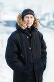 一个年轻西伯利亚人在冷的冬日,有毛皮敞篷的佩带的温暖的下来夹克的画象,垂直 雪,霜 免版税库存照片