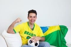 一个巴西足球迷的目标庆祝在沙发的 库存照片