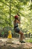 一个滑轮的一个女孩在绳索公园 免版税库存图片