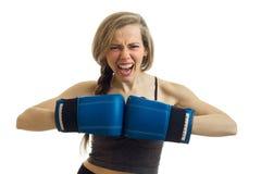 一个年轻运动女孩在白色背景以前尖叫并且握在拳击手套的手隔绝 免版税库存照片